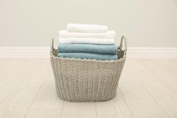 Wicker basket with folded towels on floor in room