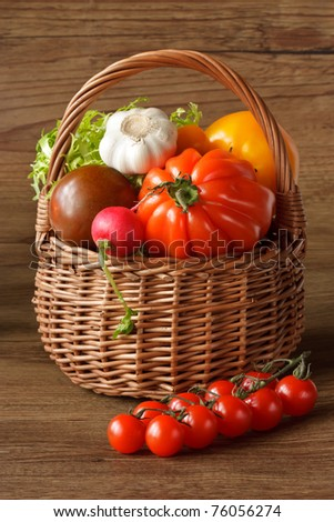 Wicker basket with fresh vegetables on a wooden table.
