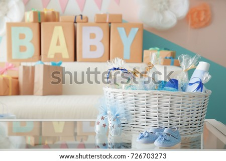 Wicker basket with gifts for baby shower party on table indoors Stockfoto ©