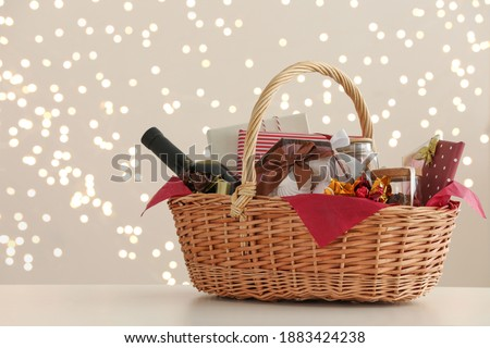 Wicker basket with gifts, wine and food against blurred festive lights. Space for text Stockfoto ©