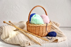 Wicker basket with knitting yarn, clothes and needles on table