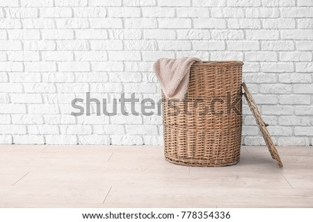 Wicker basket with laundry on floor against brick wall #778354336