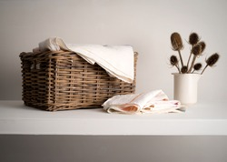 Wicker Basket with linen inside, on a shelf with a rustic bottle and dried teasel plant