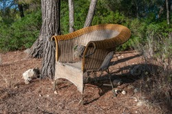 Wicker chair abandoned in the middle of a forest, at sunset