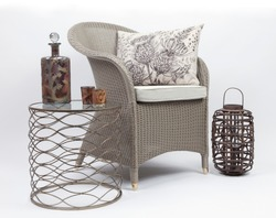 Wicker chair and cushions with a side table and wicker candle holder on a white background