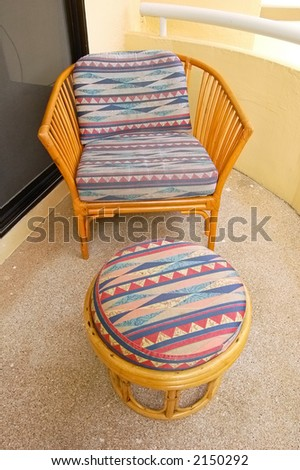Wicker chair and footstool on a balcony