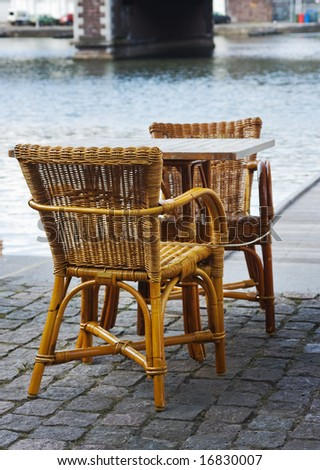 wicker chairs of an open-air cafe installed on cobblestone pavement