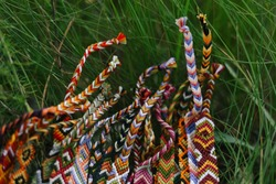 Wicker colored handmade bracelets from thread lie in the grass up close. Background for needlework