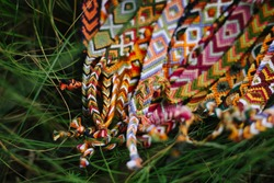 Wicker colored handmade bracelets lie in the grass up close. Background for needlework