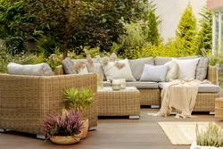 Wicker furniture on a wooden terrace of modern house