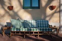 Wicker garden furniture with soft cushions on patio, in evening light