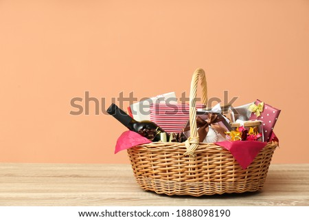 Wicker gift basket with bottle of wine on wooden table. Space for text Stockfoto ©