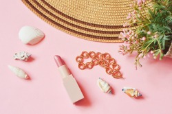 Wicker hat, pink lipstick, gold bracelet, flowers and seashells. Flat lay composition beauty still life photography. Spring and summer makeup