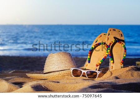 Wicker hat, sandal and glasses on the sandy beach