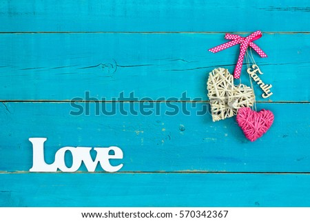 Wicker Heart Pink Rope And Family Hanging On Antique Rustic Teal Blue Wood Background