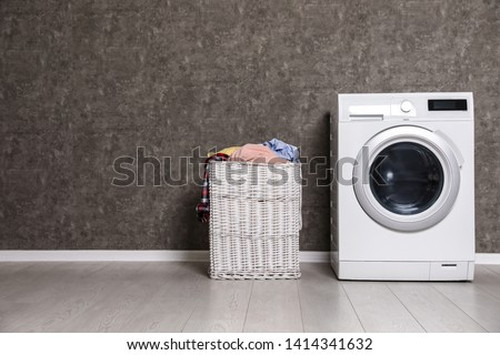 Wicker laundry basket full of dirty clothes and washing machine near color wall. Space for text #1414341632