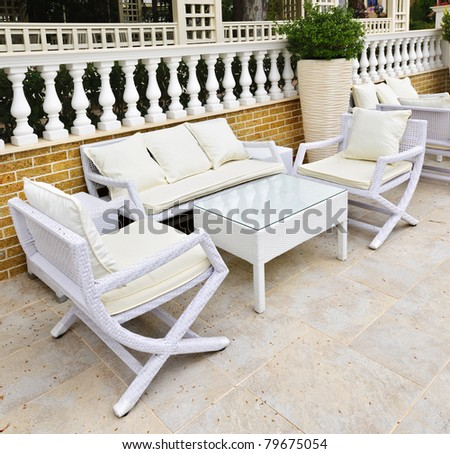 Wicker patio furniture outdoor in area paved with natural stone