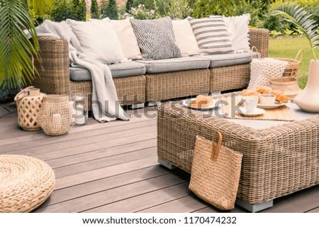 Wicker patio set with beige cushions standing on a wooden board deck. Breakfast on a table on a backyard porch. - Shutterstock ID 1170474232
