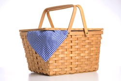 Wicker picnic basket on a white background with blue gingham tablecloth