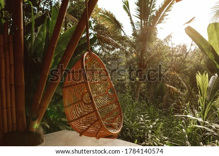 Wicker rattan hanging chair on wooden bamboo terrace in the jungle, nature view. Rattan lounge hanging chair at the balcony with green nature background