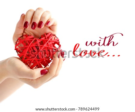 Wicker red heart in woman's hands on white background. Closeup heart in hand of girl with red manicure. Happy Valentines day, love concept. Space for your text.