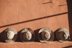 Wicker straw hats on background of terracotta color wall in Morocco. Sun light and shadows.