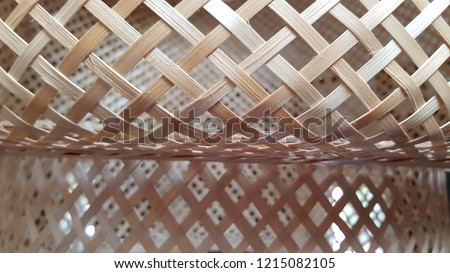 Wicker straw lampshade closeup. Natural straw lattice texture with backlighting. Shaped lattice background. Light beige grid pattern. Geometric shapes and lines abstract backdrop. 3D shapes.