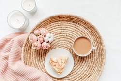 Wicker tray, cup of coffee with milk, piece of cake, rose flowers, candles, pink knitted plaid or blanket. Breakfast in bed. Stylish home interior decor. Flat lay, top view.