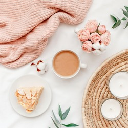 Wicker tray, cup of coffee with milk, piece of cake, rose flowers, eucalyptus branch, candles, pink knitted plaid or blanket. Breakfast in bed. Stylish home interior decor. Flat lay, top view.