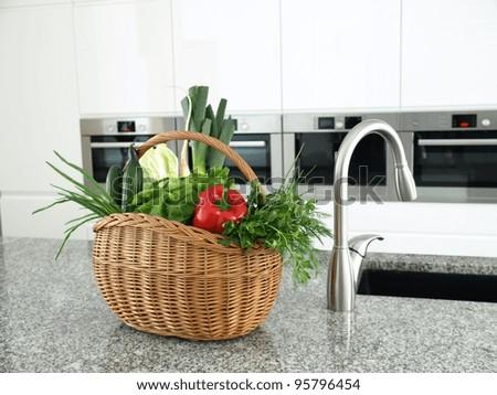 Wickerwork basket full of vegetables in a modern kitchen interior