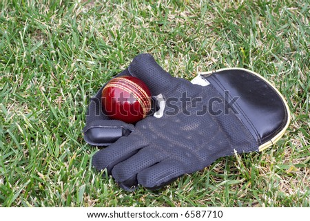 Wicket keeping glove with a new red cricket ball before play.