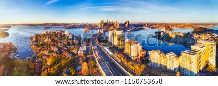Wide aerial panorama of Sydney city CBD landmark around Harbour viewed from North Sydney along Warringah freeway lit by warm morning light. #1150753658