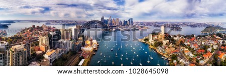 Wide aerial panorama of Sydney city CBD landmarks on shores of Sydney Harbour from Lower North Shore to distant Barangaroo.
