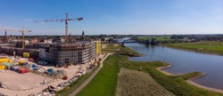 Wide aerial panoramic view on a construction site of the new Noorderhaven neighbourhood on the left and river IJssel that flows passed Hanseatic Dutch city of Zutphen on the right