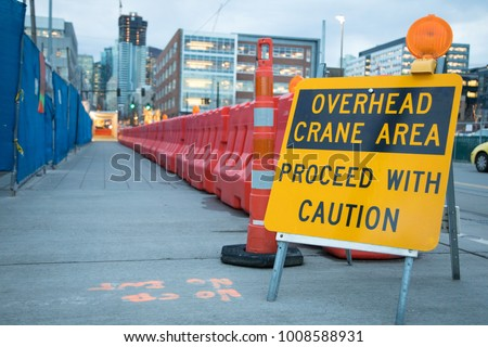 Wide angle close up on a construction sign warning, Overhead Crane Are Proceed With Caution, with sidewalk leading away in background