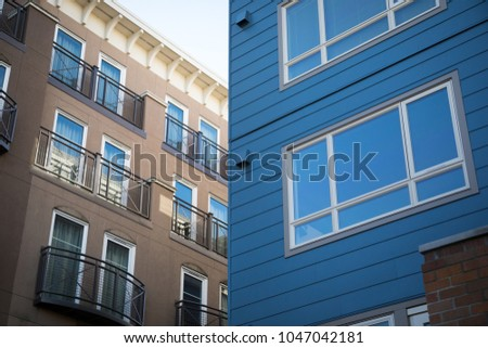 Wide angle close up on a modern blue apartment building, and a brown stucco hotel with balconies in the background