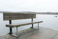 Wide angle close up on a wood park bench at the end of a dock with lake water and shore on the horizon in the background
