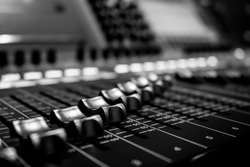 Wide angle closeup of Pro Audio Digital Mixing Sound Console. Silver White Faders and black control Console