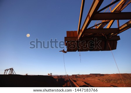 Wide angle concept of industry rope access technician inspector wearing fall body safety harness hardhat abseiling inspecting up side down defect concrete spalling counterweight fall moon background