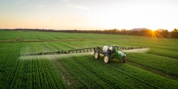 Wide angle image of a crop spray machine spraying chemicals on wheat crop on a farm in south africa