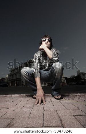 Wide angle image of a man squatting on the street
