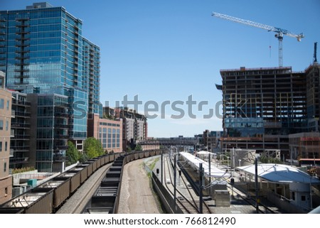 Wide angle industrial cityscape above empty coal train cars extending into the distance, with modern apartment buildings and skyscrapers #766812490