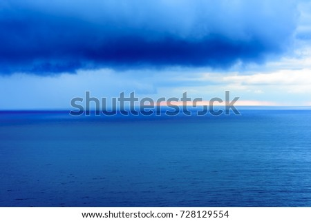 Wide angle long exposure panorama landscape seascape vista with shades of green, aqua, turquoise and blue under blue skies with low lying puffy clouds.  #728129554