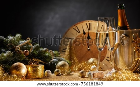 Wide angle New Years banner with flutes and a bottle of champagne in front of a clock counting down to midnight and copy space above assorted gold seasonal holiday decorations