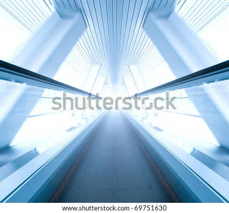 wide angle of moving blue escalator inside contemporary airport