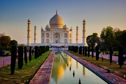 Wide angle of Tajmahal with it's reflection in the fountain pond, one of the seven wonder partially lit under dramatic sunrise