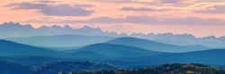 Wide angle panorama autumn forest,misty hills mountain tops in pink dawn