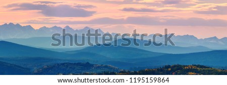 Wide angle panorama autumn forest,misty hills mountain tops in pink dawn #1195159864