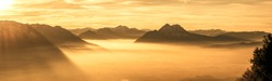 wide angle panorama from mt. gaisberg in salzburg, overlooking salzburg covered by fog during golden hour