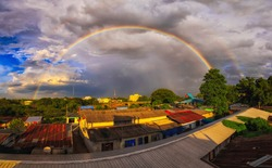 Wide angle Panorama image of Rainbow and storm cloud over the town of Uttaradit, Thailand.